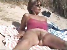 Moglie amatoriale matura mostra la figa pelosa su una spiaggia
